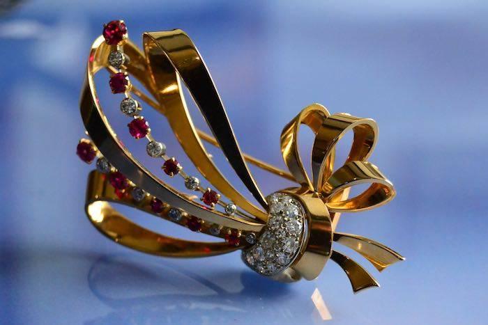 Broche noeud en or 18k et platine sertie de diamants et rubis
